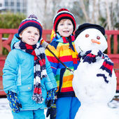 Two little friends making a snowman, playing and having fun with — Stock Photo