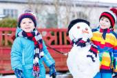 Two little siblings boys making a snowman, playing and having fu — Stock Photo