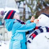 Funny kid boy in colorful clothes making a snowman, outdoors — Stock Photo
