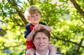 Father carrying child on his shoulders in the park — Stock Photo