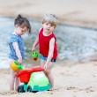 Little toddler boy and girl playing together with sand toys near — Stock Photo #66937455