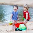 Little toddler boy and girl playing together with sand toys near — Stock Photo #66937475