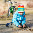 Cute little boy playing with wooden sticks in city park, outdoor — Stock Photo #68681525