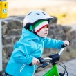 Little preschool kid boy riding with his first green bike — Stock Photo #68681553