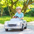 Little boy driving big toy old car, outdoors — Stock Photo #68690913