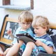 Two happy twins boys friends holding tablet pc, outdoors. — Stock Photo #68691217
