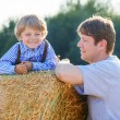 Young father and his little son having fun on yellow hay field i — Stock Photo #68691351