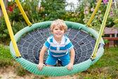 Adorable toddler boy having fun chain swing on outdoor playgroun — Stock Photo