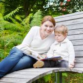 Little boy and his mother sitting on bench in park and reading b — Stock Photo