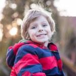 Portrait of happy little kid boy in red jacket, outdoors — Stock Photo #69548185
