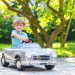 Little boy driving big toy old car, outdoors — Stock Photo #69549101
