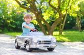 Little boy driving big toy old car, outdoors — Foto de Stock