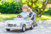 Two funny little friends playing with big old toy car — ストック写真