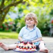 Little boy celebrating his birthday in home's garden with big ca — Stock Photo #69550321