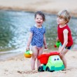 Little toddler boy and girl playing together with sand toys near — Stock Photo #70482347