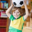 Little funny kid boy playing with a football at home — Stock Photo #70482687