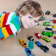 Little blond kid boy playing with lots of toy cars indoor — Stock Photo #70484757