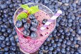 用草和薄荷枝的玻璃罐子里的蓝莓果昔 — 图库照片
