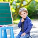 Little boy at blackboard learning to write — Stock Photo #71063911
