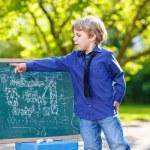 Little boy at blackboard learning to write — Stock Photo #71064049