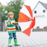 Little blond kid boy walking with big umbrella outdoors  — Stock Photo #71065883
