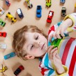 Funny little boy playing with lots of toy cars indoor — Stock Photo #71066095