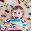 Adorable little boy playing with lots of toy cars indoor — Stock Photo #71066155