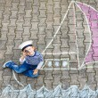 Little kid boy having fun with ship picture drawing with chalk — Stock Photo #71066531