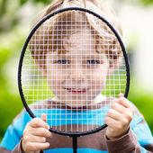 Niño lindo chico divertido jugar bádminton en el jardín doméstico — Foto de Stock