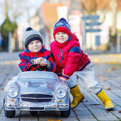 Two happy sibling boys playing with big old toy car, outdoors — Stockfoto