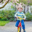 Adorable little kid boy driving his first bike or laufrad — Stock Photo #74094347