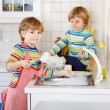 Two funny little boy friends washing dishes in domestic kitchen — Stock Photo #74097593