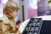 Cute little kid boy at optician store during choosing his new gl — Stock Photo