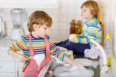 Two little blond kid boys washing dishes in domestic kitchen — Stock Photo