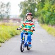 Kid boy in helmet riding his first bike, outdoors — Stock Photo #75871579