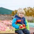 Funny toddler boy sitting on tractor with red apples — Stock Photo #75872777