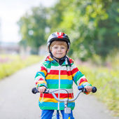 Kid boy in helmet riding his first bike, outdoors — Stock Photo