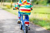 Little child in colorful clothes on bicycle — Stockfoto