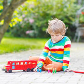Active kid boy playing with red school bus and toys — Stock Photo