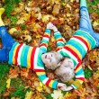 Two blond boys lying in autumn leaves in colorful clothing. Happy siblings having fun in autumn park on warm day — Stock Photo #77054595