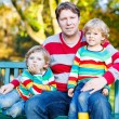 Two little kid boys and young father sitting together, autumn, o — Stock Photo #77054673