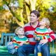 Two little kid boys and young father sitting together, autumn, o — Stock Photo #77054703