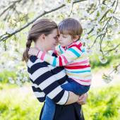 Young mother and little kid boy in blooming garden — Stock Photo