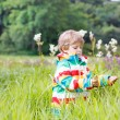 Little blond boy with lot of wild flowers — Stock Photo #79444158