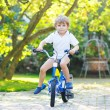 Little preschool kid boy riding with bicycle in summer — Stock Photo #79444576