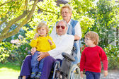Two little kid boys, their grandmother and grandfather in wheelc — Stock Photo
