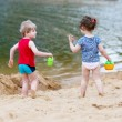 Little toddler boy and girl playing together with sand toys near — Stock Photo #80849302