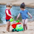 Little toddler boy and girl playing together with sand toys near — Stock Photo #80849340