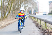 Kid boy in safety helmet and colorful raincoat riding bike, outd — Stock Photo