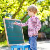 Little boy at blackboard learning to write — Stock Photo